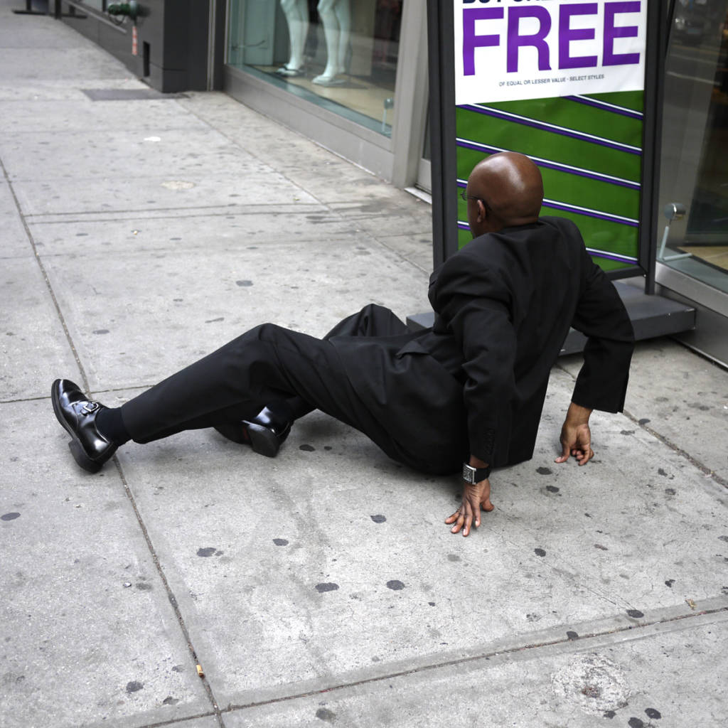 man in suit fallen on sidewalk