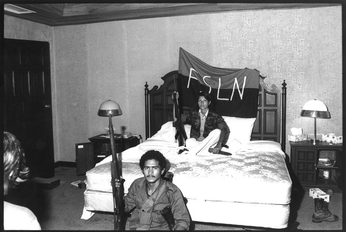 Two men sitting on a bed