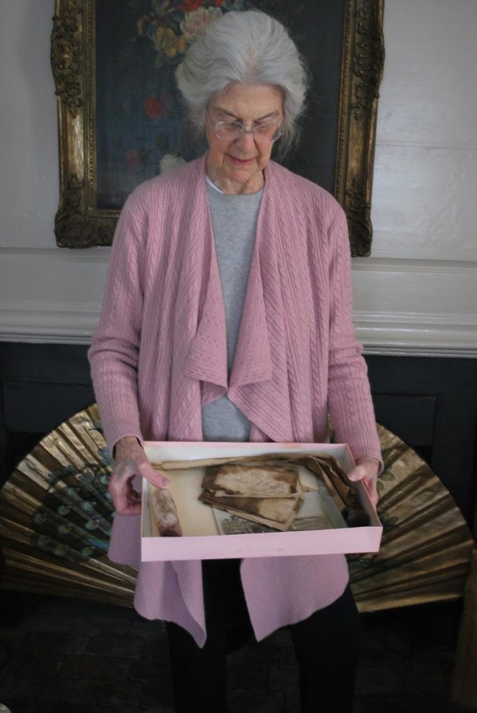 Connie Congdon holds a box filled with five artifacts a mason found in the chimney of her Nantucket home: 19th-century letters; a man's shirt collar; a pipe; a laudanum bottle; and a plaster phallus.