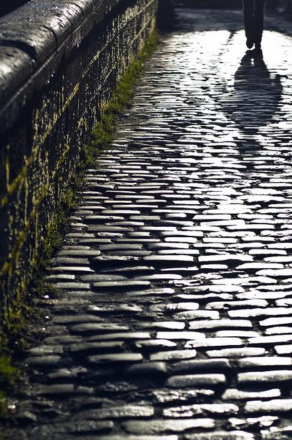 Figure walking down a cobblestone street