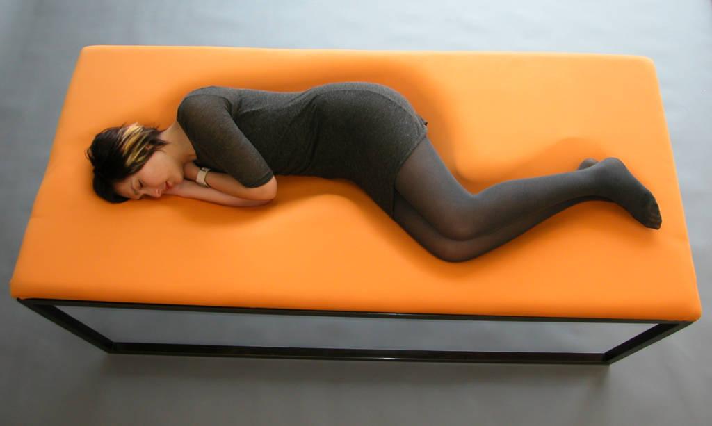 Woman lying on orange chair