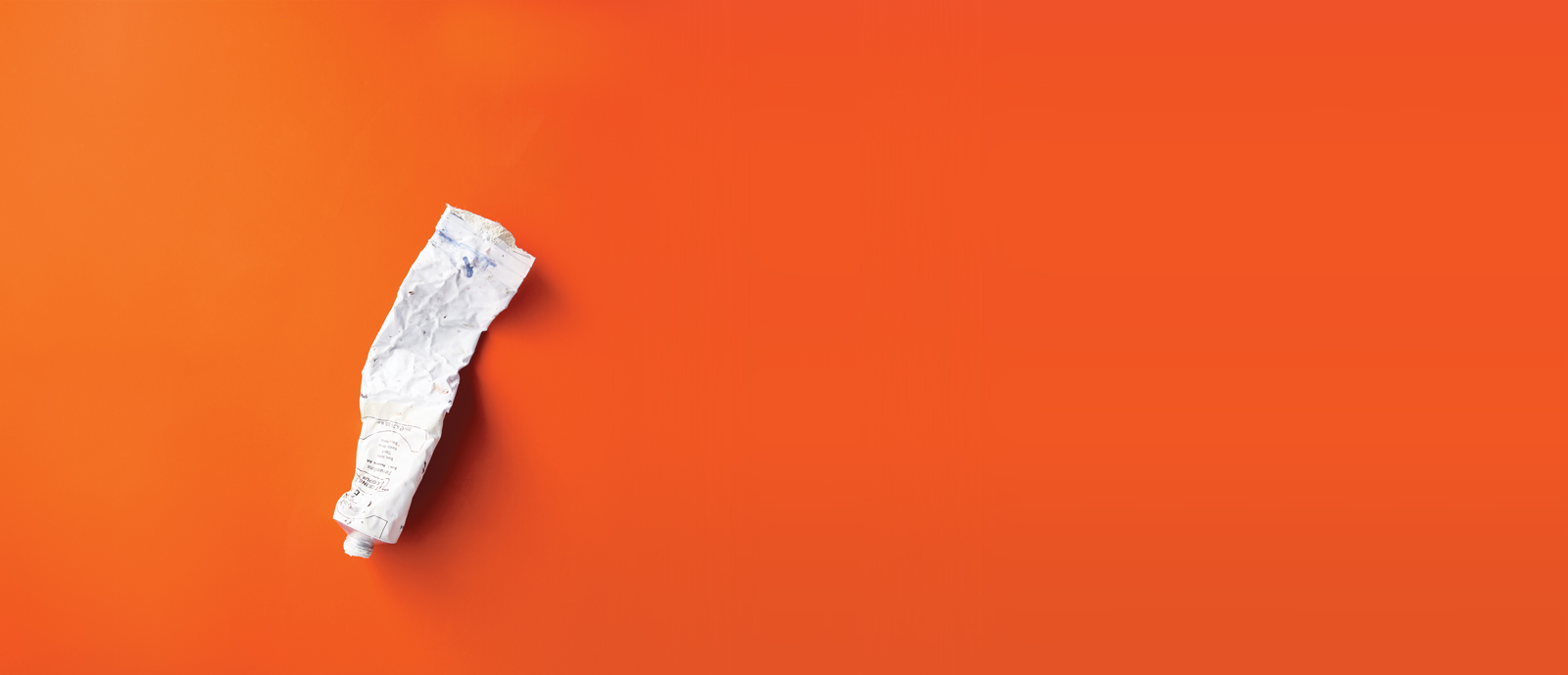 Cover image from Issue 14, a crinkled tube of white paint on an orange background