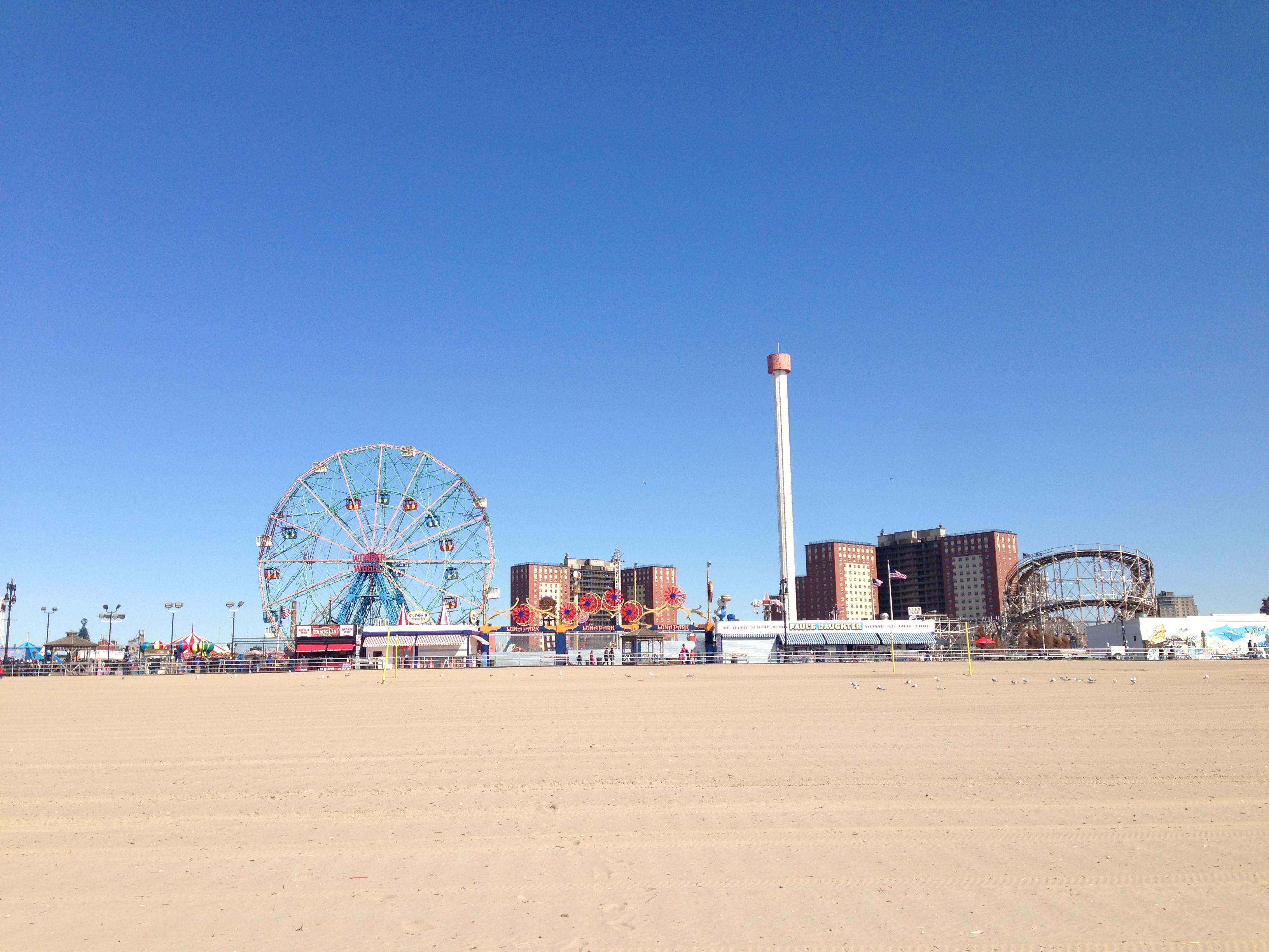View of Coney Island boardwalk and ferris wheel from the beach