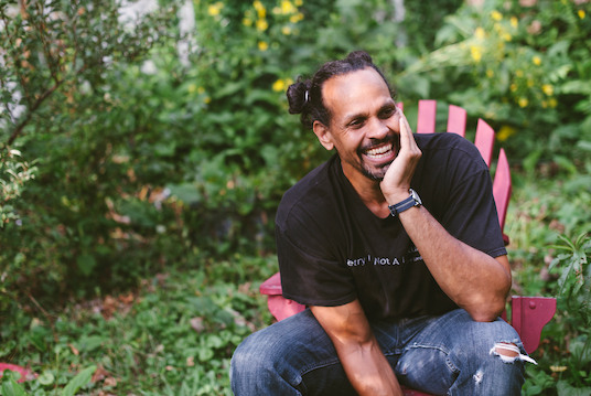 headshot of ross gay sitting in a garden