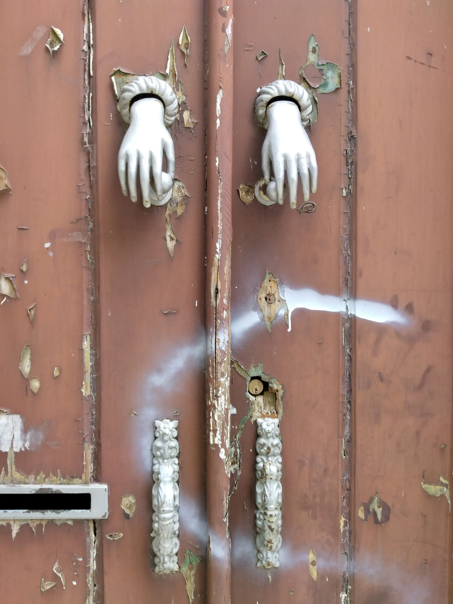 Image of doors with statue hands.