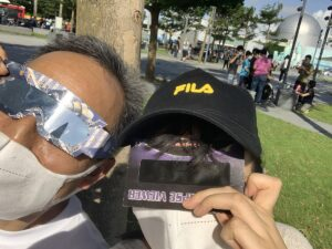 Image of people watching the eclipse through special glasses.