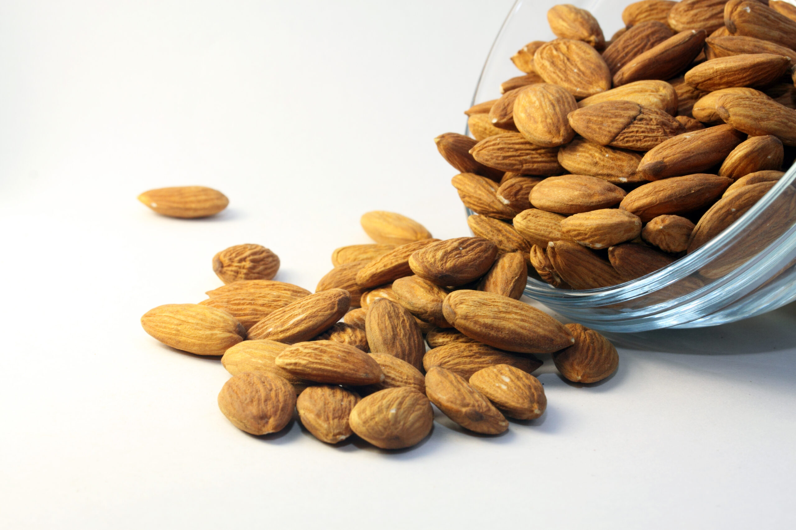 Image of almonds pouring from a glass bowl.