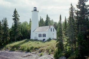 Image of a lighthouse surrounded by conifer trees.