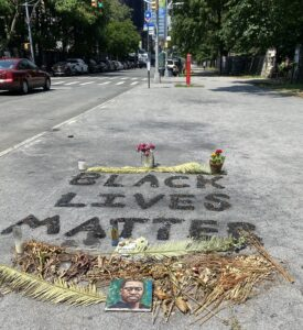 Image of Black Lives Matter written on the ground with dry flowers and a picture of George Floyd.