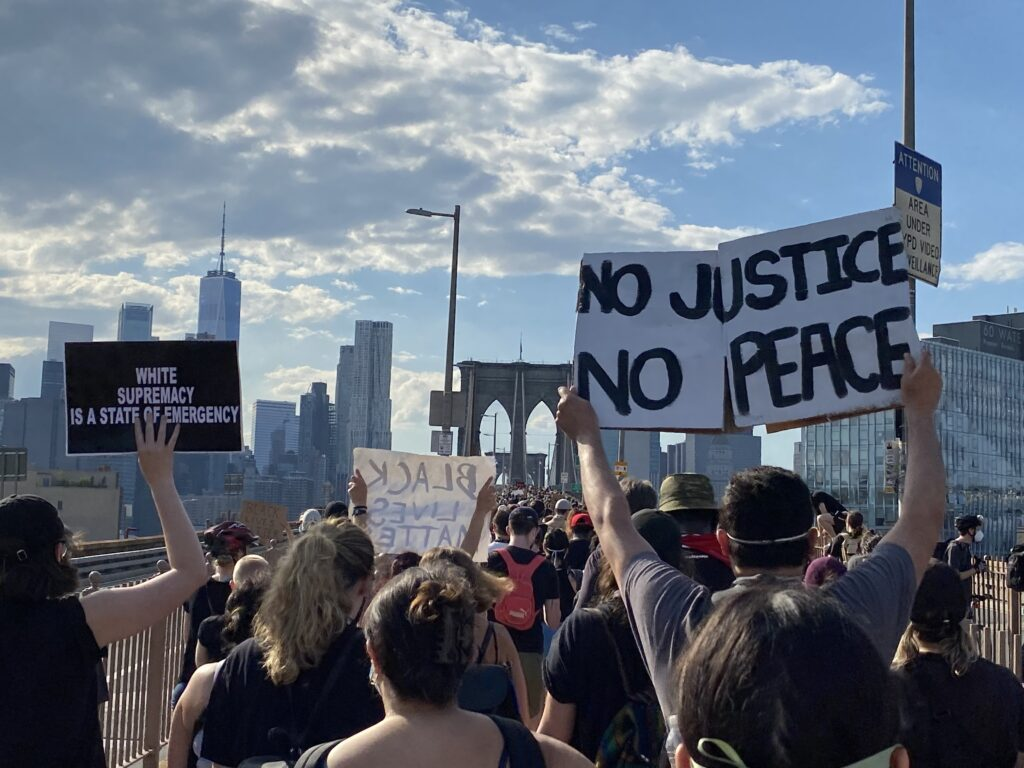 """Image of a protest on the Brooklyn Bridge in NYC, with someone holding up a sign saying """"No Justice, No Peace."""""""