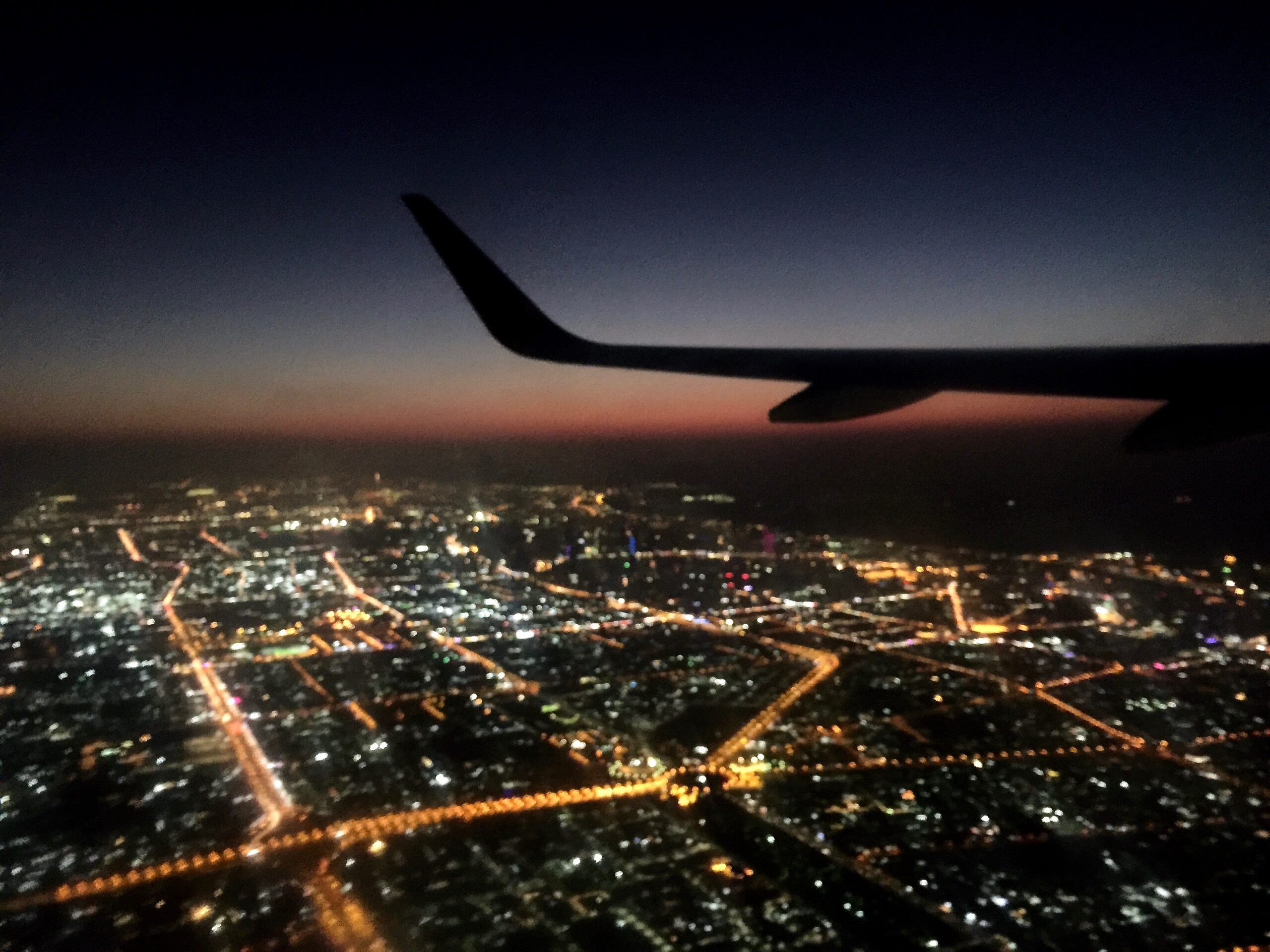 A plane flies over a city at night